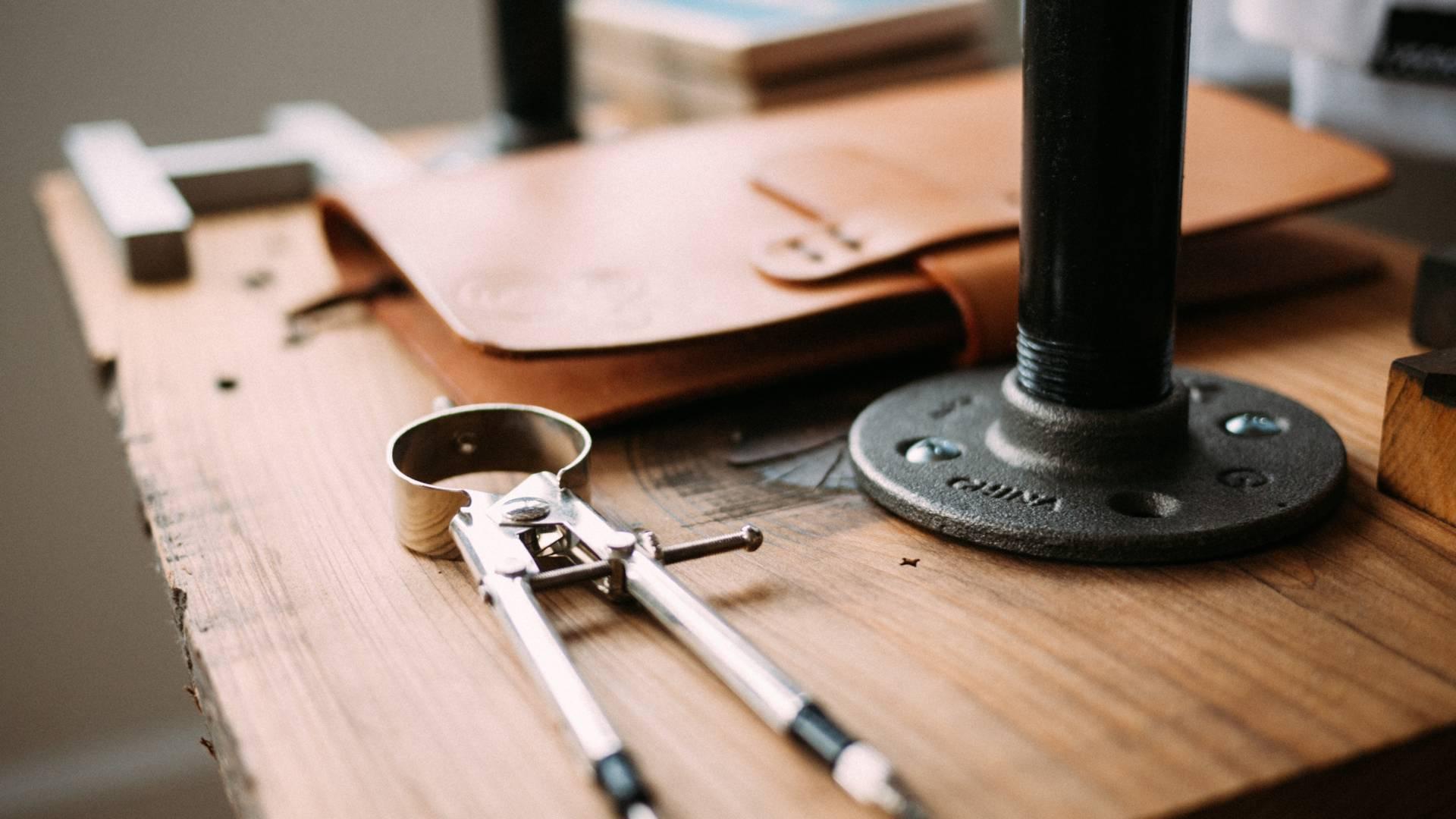 Schreibtisch mit Zirkel und Mappe - Quelle: Jeff Sheldon via unsplash.com